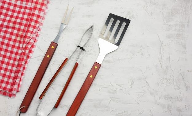 Metalowe przybory kuchenne z drewnianymi uchwytami do grilla na białym tle