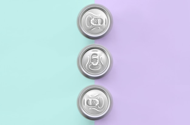 Metalowe puszki piwa na tle tekstury moda pastelowe fioletowe i niebieskie kolory papieru