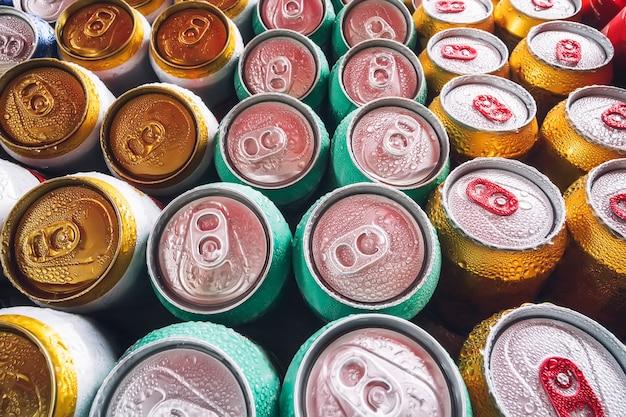 Metalowe puszki piwa z kostkami lodu w mini lodówce, z bliska. dużo aluminiowych puszek w lodzie w otwartej lodówce. krople wody na zimnej puszce napoju.