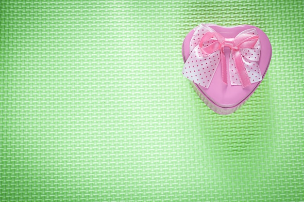 Metalowe, różowe pudełko w kształcie serca ze wstążką na zielonej powierzchni