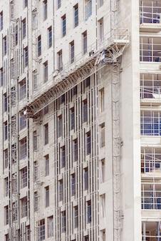 Metalowe rusztowania bezpieczeństwa w budowie wieżowca.