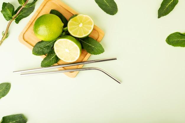 Metalowe słomki wielokrotnego użytku na pastelowym tle. świeże owoce wapna i mięty leżą na drewnianym stojaku. podkreślają zielony kolor i fruts. produkty środowiskowe wielokrotnego użytku, zero odpadów. produkty eco