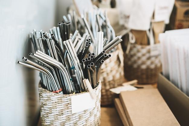 Metalowe słomki wielokrotnego użytku ze stali nierdzewnej na tle z innymi towarami w sklepie spożywczym bez plastiku