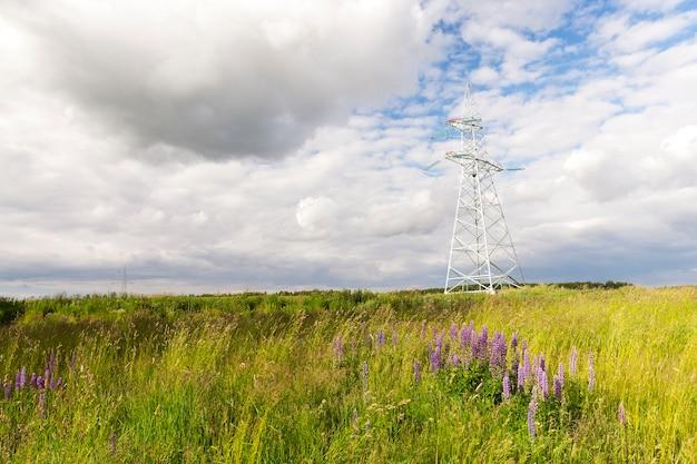 Metalowe słupy do linii elektrycznych w terenie. zbliżenie w lecie. skoncentruj się na biegunie. w tle niebo z chmurami