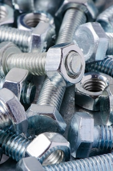 Metalowe śruby i nakrętki. narzędzia do pracy i naprawy. makrofotografia.