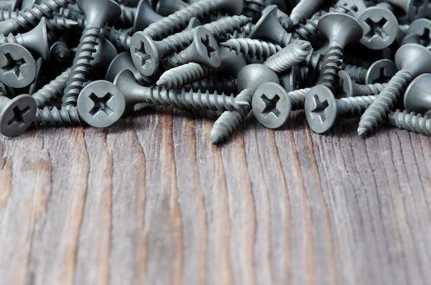 Metalowe śruby na drewnianym stole. narzędzie do mocowania i naprawy.