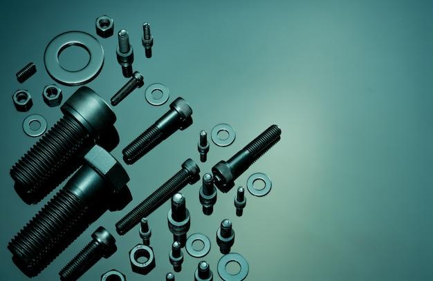 Metalowe śruby, nakrętki i podkładki. wyposażenie elementów złącznych. narzędzia sprzętowe. śruba dwustronna, podkładki płaskie, nakrętki sześciokątne i śruby z łbem sześciokątnym w warsztacie. zastosowanie łączników gwintowanych w inżynierii samochodowej.