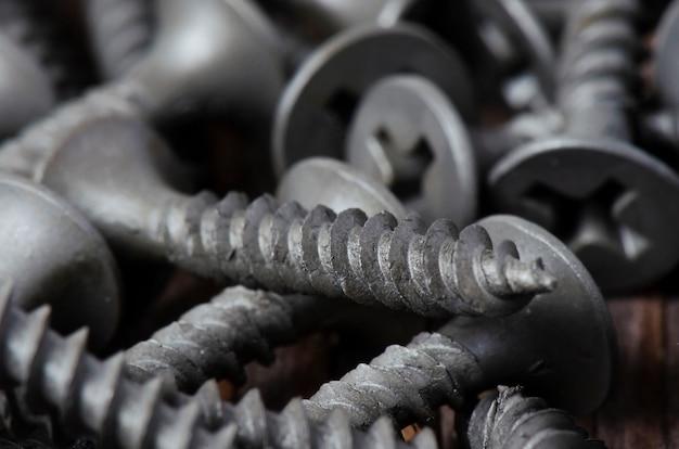 Metalowe śruby z bliska na drewnianym stole. narzędzia do mocowania i naprawy. makrofotografia.
