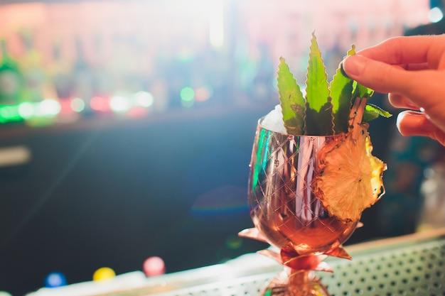 Metalowe szklanki świeżych letnich koktajli ozdobione owocami i oparami na blacie barowym.