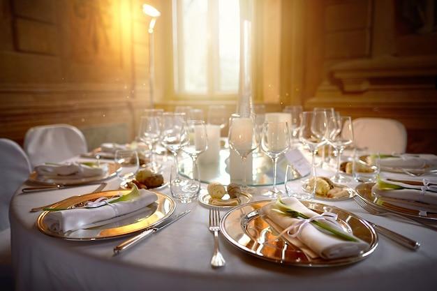 Metalowe talerze z serwetkami i kwiatami w restauracji na tle szklanek i okien