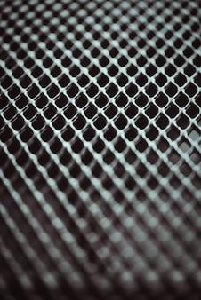 Metalowe tło. tekstura kraty z siatką małych komórek. selektywny punkt ostrości.