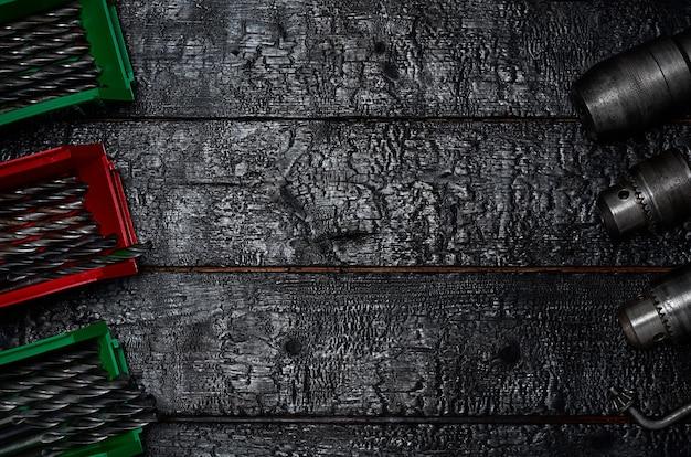 Metalowe uchwyty i wiertła w pudełkach na czarnej drewnianej powierzchni