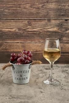Metalowe wiadro czerwonych świeżych winogron i kieliszek białego wina na marmurowej powierzchni.