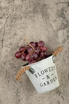 Metalowe wiadro czerwonych świeżych winogron na marmurowym stole.
