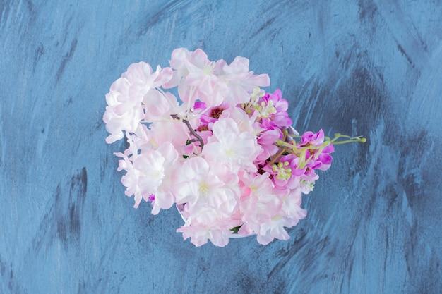Metalowe wiadro pełne pięknych kolorowych kwiatów na niebiesko.