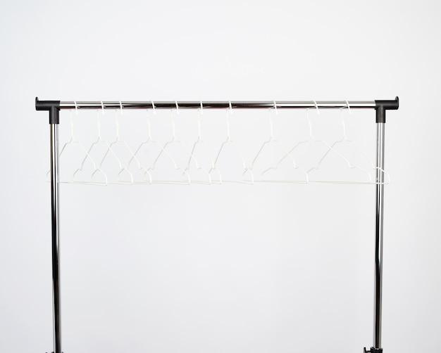 Metalowe wieszaki zawieszone są na chromowanym drążku