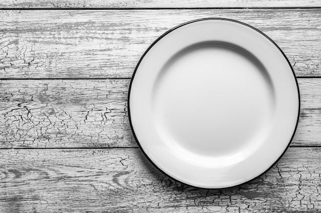 Metalowy biały talerz z niebieskim obramowaniem na drewnianym stole