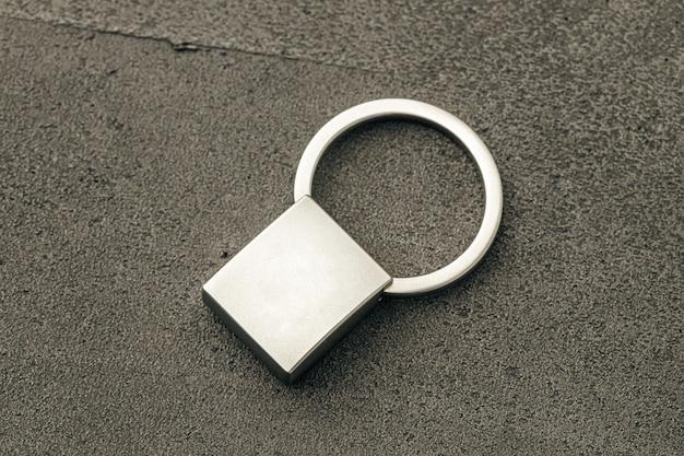 Metalowy breloczek na ciemnym tle betonu z bliska
