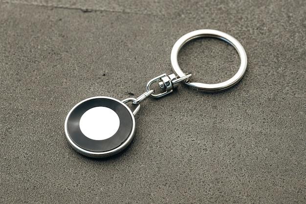 Metalowy brelok do kluczy na ciemnym betonowym tle