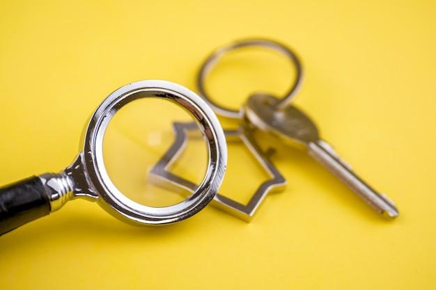 Metalowy brelok w kształcie domu z metalowym kluczem pod lupą na żółtym tle.