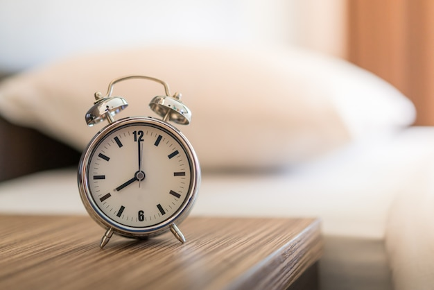 Metalowy budzik na białym łóżku 8 rano.