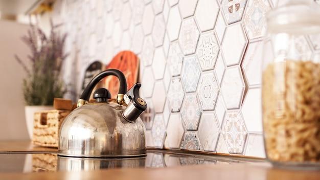 Metalowy czajnik na kuchence. nowoczesna przytulna kuchnia.