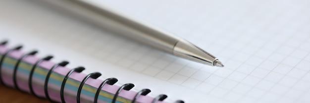 Metalowy długopis leżący na notatniku zbliżenie studium i koncepcja edukacji