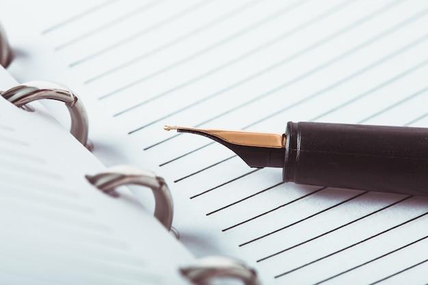 Metalowy długopis z piórkiem na papierze w linie w zeszycie