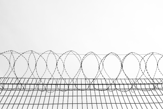 Metalowy drut kolczasty na ścianie więzienia. symbol ograniczenia wolności.