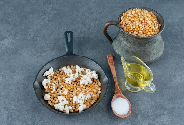Metalowy dzbanek i patelnia wypełnione ziarnami kukurydzy i kilkoma prażonymi popcornami