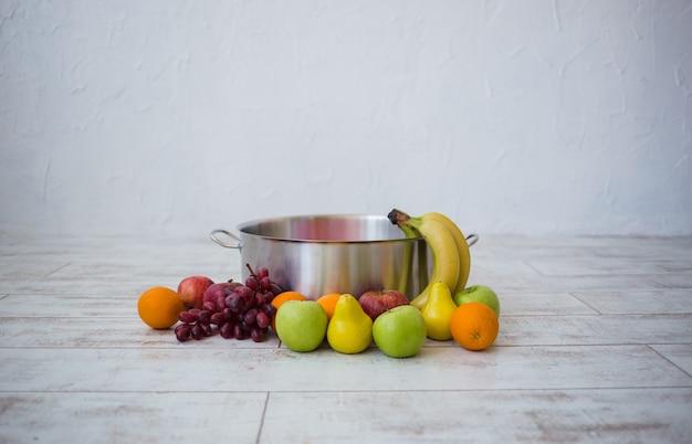 Metalowy garnek z różnymi owocami na białym z miejscem na tekst