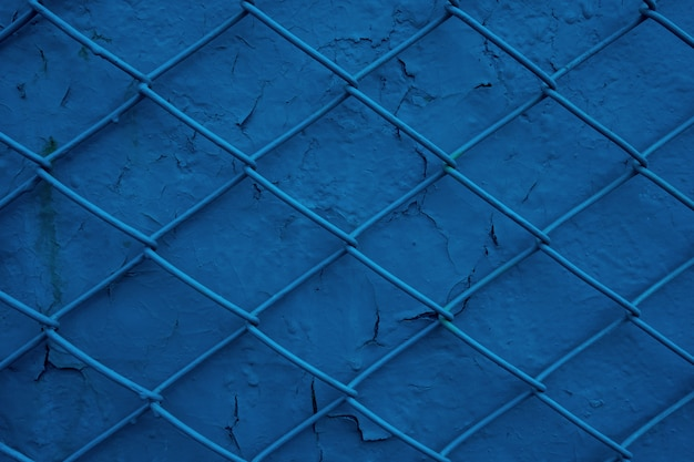 Metalowy grill z drutu na tle starej niebieskiej ściany z łuszczącą się farbą. tekstura siatki jako koncepcja zamknięcia, nie wolności, ochrony i bezpieczeństwa
