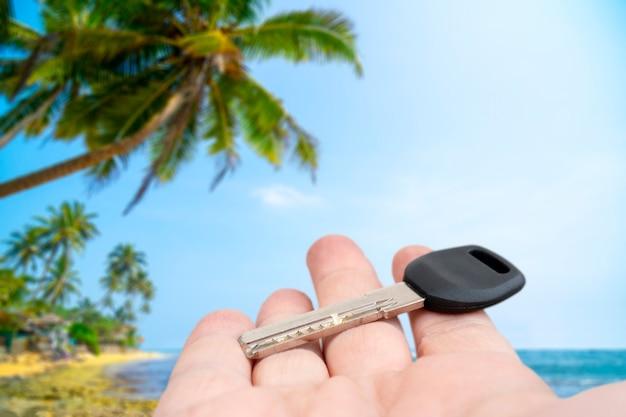 Metalowy klucz do drzwi w męskiej dłoni. sprzedaż i wynajem nieruchomości.