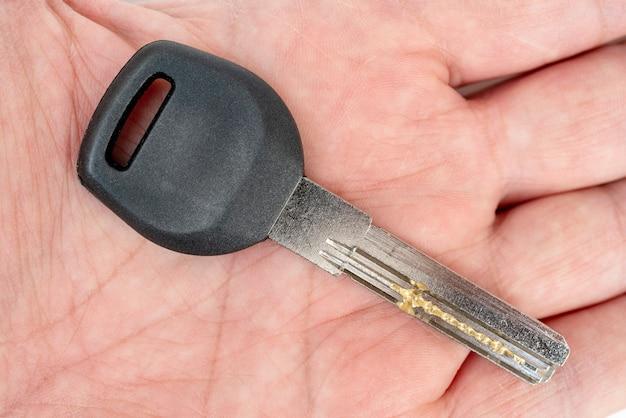 Metalowy klucz do drzwi w męskiej dłoni
