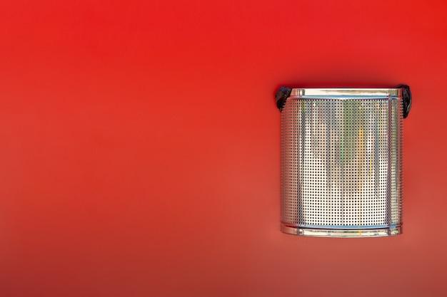 Metalowy kosz na śmieci na czerwonej ścianie