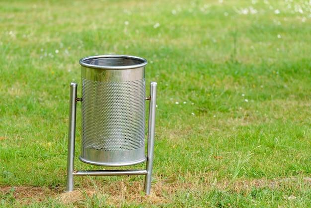 Metalowy kosz na śmieci na zielonym trawniku w parku z bliska