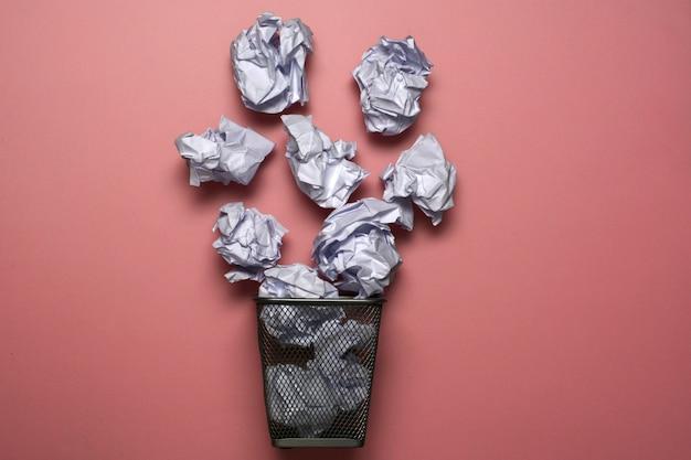 Metalowy kosz na śmieci z papierem. kosz na papier z koncepcją.