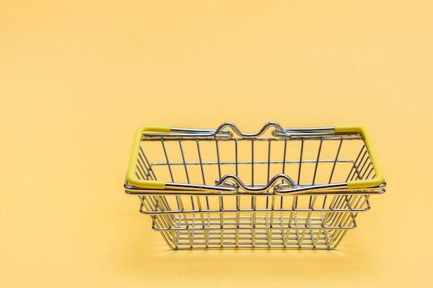 Metalowy kosz na zakupy w sklepie na żółtym tle. sprzedaż prezentów w czarny piątek. skopiuj miejsce