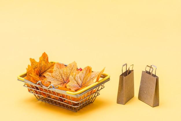 Metalowy kosz na zakupy w sklepie wypełnionym jesiennymi liśćmi i kilka rzemieślniczych papierowych toreb na żółtym tle. sprzedaż prezentów w czarny piątek. skopiuj miejsce