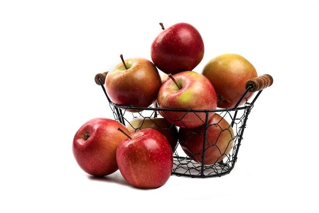 Metalowy kosz świeżych dojrzałych jabłek na białym tle.