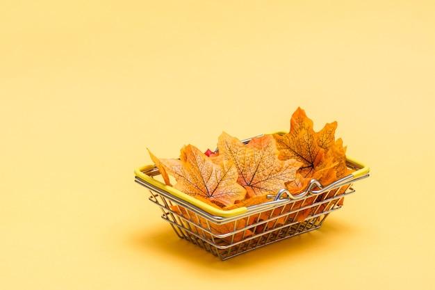 Metalowy koszyk na zakupy w sklepie wypełnionym jesiennymi liśćmi na żółtym tle. wyprzedaż prezentów w czarny piątek