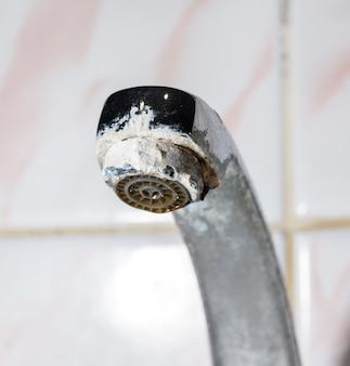Metalowy kran w łazience z białymi osadami, z bliska