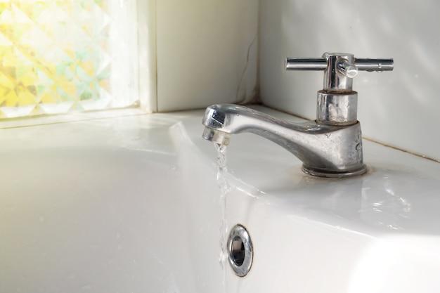 Metalowy kran z włączonym przepływem wody w publicznej toalecie. porządkowanie koncepcji.