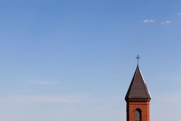 Metalowy krzyż religijny na starej wieży z czerwonej cegły i dachu kościoła, na tle błękitnego nieba element budynku