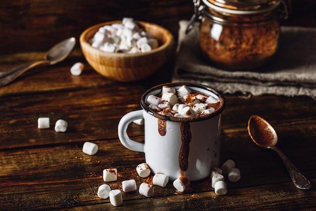 Metalowy kubek kakao z piankami. słoik kakao w proszku i miska marshmallow