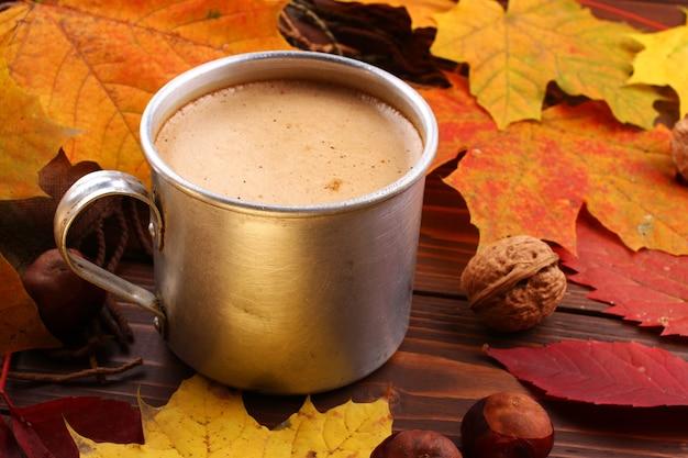 Metalowy kubek z cappuccino i jesiennymi liśćmi