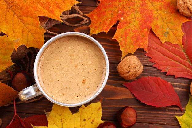 Metalowy kubek z cappuccino, orzechami i jesiennymi liśćmi
