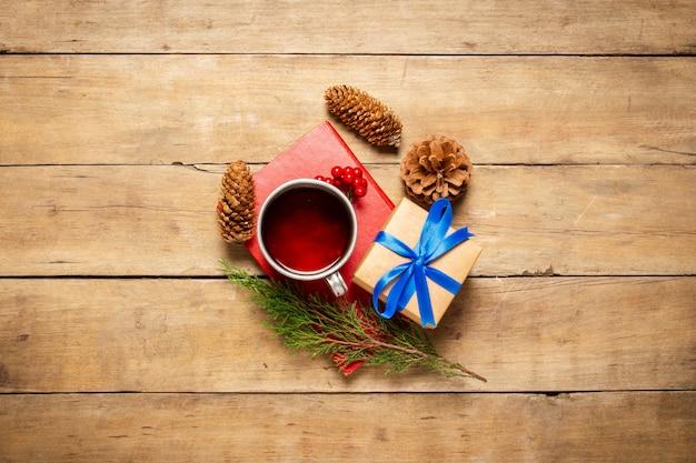 Metalowy kubek z gorącą herbatą, rożkami, gałązką choinki, książką i prezentem na drewnianym tle. zimowy nastrój, boże narodzenie, ferie zimowe. leżał płasko, widok z góry