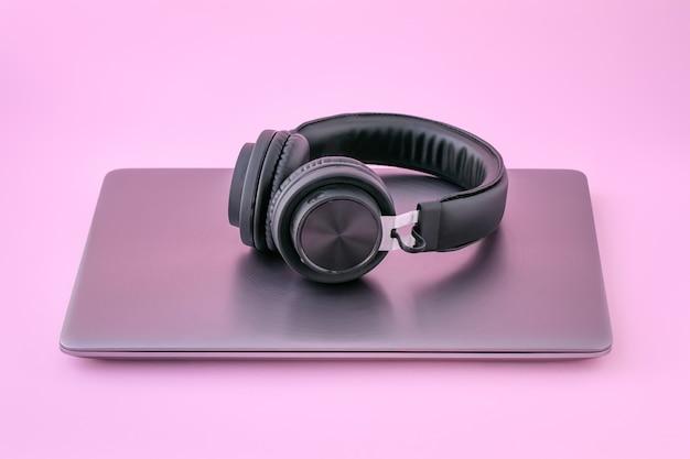Metalowy laptop i czarne słuchawki. zamknięty notes. pojęcie samokształcenia.