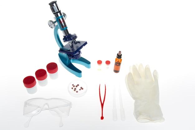 Metalowy mikroskop laboratoryjny i probówki z płynem na białym tle